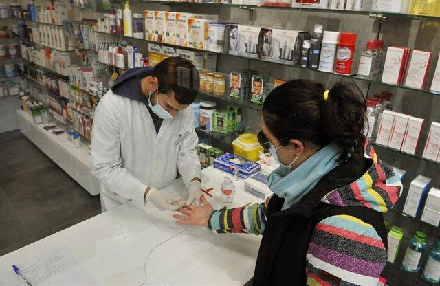 Un farmacéutico realiza una prueba serológica de Covid-19 en la Farmacia Mónica Muradas, en O Carballiño, Ourense, Galicia (España), a 22 de octubre de 2020.