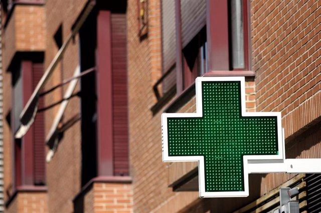 Una señal luminosa de la cruz verde a la entrada de una farmacia.