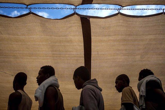 Refugiados y migrantes rescatados en el mar Mediterráneo a la espera de desembarcar en Italia