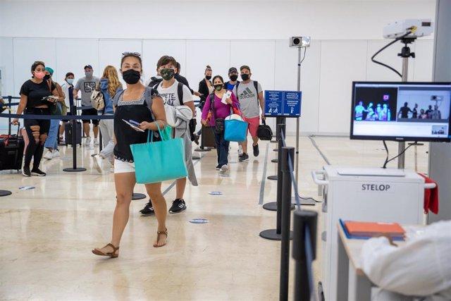 Los pasajeros que aterrizan en el Aeropuerto Internacional de Cancún son sometidos a controles de temperatura a su llegada.