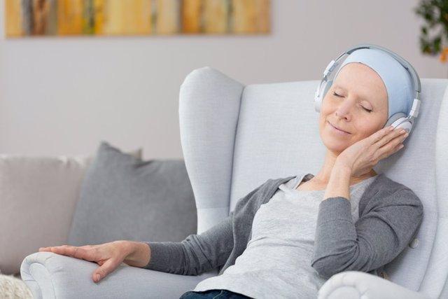 Mujer con cáncer escuchando música. Músicoterapia.