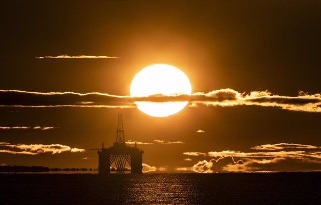 27 April 2020, Scotland, Kirkcaldy: The sun rises behind a redundant oil platform moored in the Firth of Forth near Kirkcaldy. Photo: Jane Barlow/PA Wire/dpa