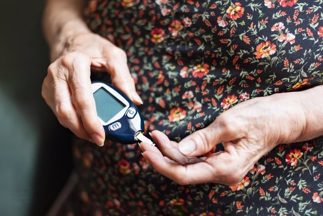 Old lady tracking her glucose levels. Health concept
