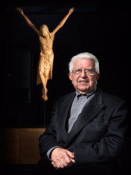 Pla mig del mossèn Jesús Tarragona, amb un crist al darrere. Imatge d'arxiu. (Vertical)