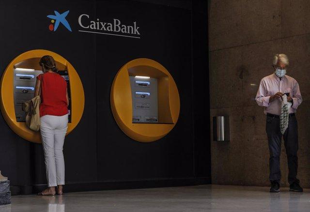 Dos personas en los cajeros dispuestos en el edificio de la sede de Caixabank, en Valencia.