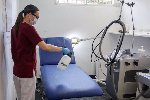 Una trabajadora desinfecta una camilla perteneciente de un centro de estética (Archivo)