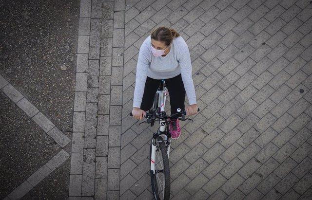 Una mujer en bicicleta, empleando una mascarilla.
