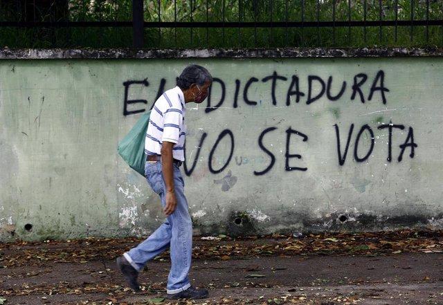 Un hombre pasea junto a un mural contra las elecciones parlamentarias de Venezuela