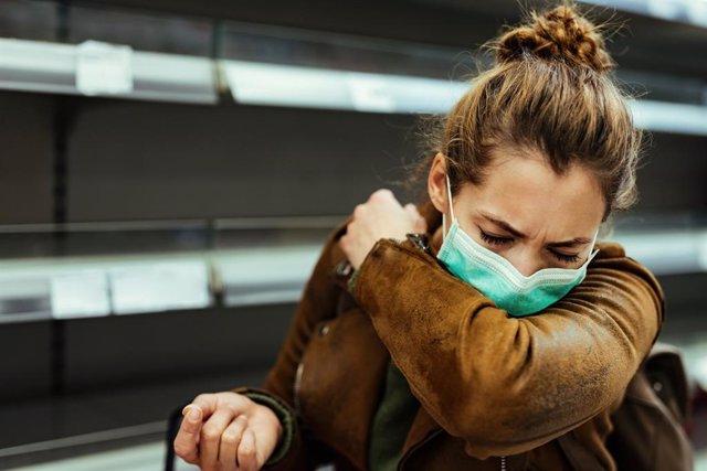 Mujer con mascarilla estornudando en el codo.