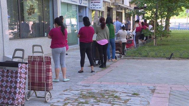 Cola de personas esperando a recibir alimentos y productos de primera necesidad, repartidos por la asociación de vecinos Manzanares-Casa de Campo a familias vulnerables.