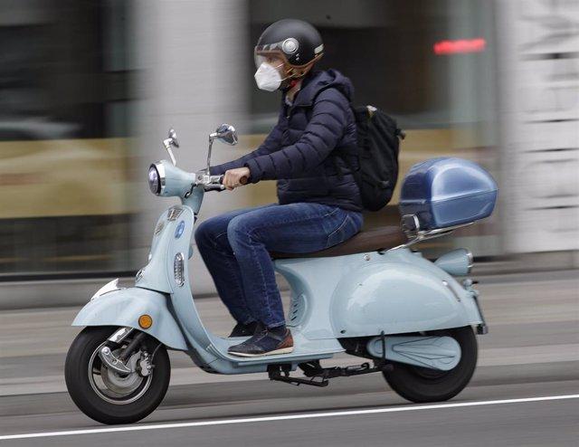 Un hombre circula en moto protegido con mascarilla por la capital. En Madrid, (España), a 12 de mayo de 2020.