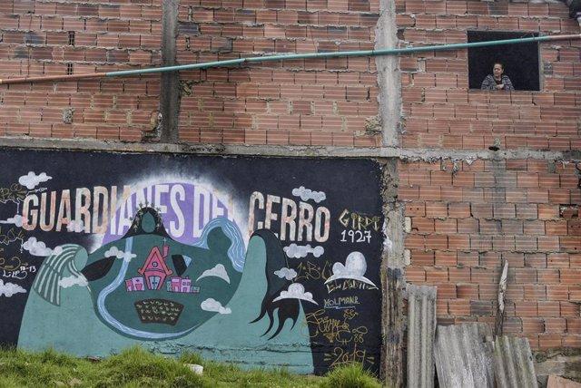 Una mujer mira desde la ventana durante el confinamiento por la pandemia de coronavirus en El Codito, un suburbio de Bogotá