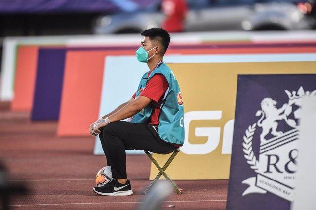 Un recogepelotas durante un partido de la liga china de fútbol.