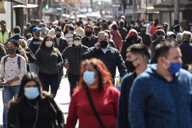 Personas con mascarilla en una calle de Santiago, en Chile