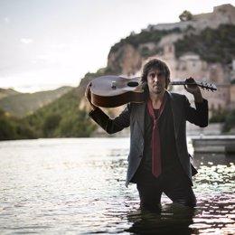 Pla americà del músic i cantant miravetà Èric Vinaixa amb la seva guitarra dins del riu Ebre. (vertical)