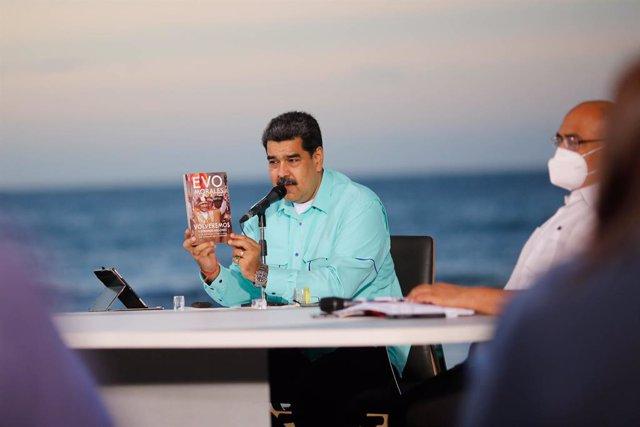 HANDOUT - 25 October 2020, Venezuela, La Guaira: Venezuelan President Nicolas Maduro holds a book by Bolivian former President Evo Morales while giving a speech at a government event in La Guaira. Photo: Jhonn Zerpa/Prensa Miraflores/dpa - ATTENTION: edit