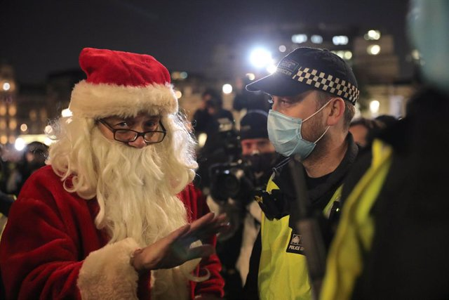 05 November 2020, England, London: A costumed man speaks with a policeman during the Million Mask March anti-establishment protest at Trafalgar Square on the first day of a four week national lockdown for England. Photo: Aaron Chown/PA Wire/dpa