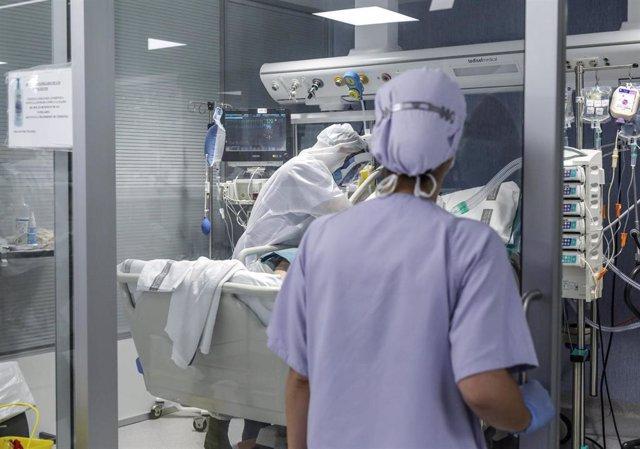 Trabajadores sanitarios totalmente protegidos atienden a un paciente con coronavirus ingresado en la UCI del Hospital Arnau de Vilanova, en Valencia, Comunidad Valenciana, (España), a 24 de abril de 2020.