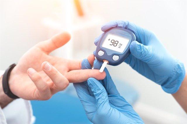 Control del nivel de glucemia en un paciente de diabetes con un glucómetro, foto de archivo.