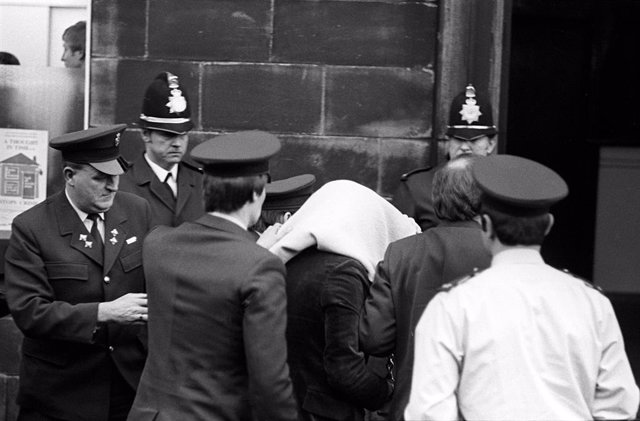 """FILED - 20 February 1981, England, Bradford: Truck driver Peter Sutcliffe (C), who were accused of murdering 13 women and the attempted murder of seven others, arrives at Dewsbury Magistrates Court. The serial killer Peter Sutcliffe, known as the """"Ripper"""
