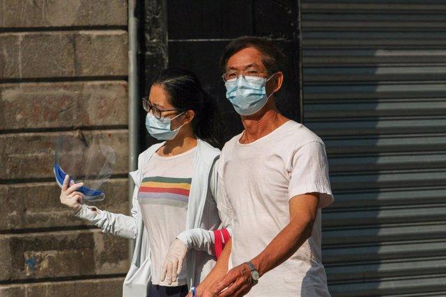 Una pareja con mascarilla pasea por las calles de Ciudad de México