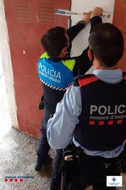 Un parell d'agents de la Guàrdia Urbana de Reus i dels Mossos d'Esquadra, precintant un immoble en un operatiu al barri Mas Pellicer en relació a fraus d'aigua i electricitat. Imatge publicada el 13 de novembre del 2020. (Vertical)