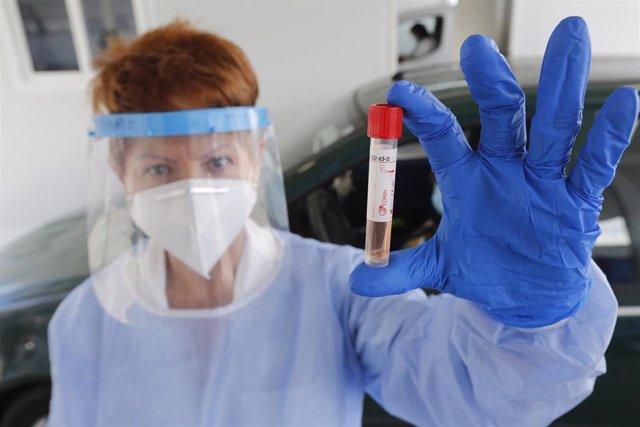 Una enfermera muestra un tubo de un test PCR.