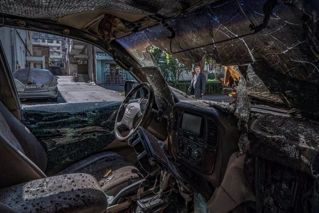 FILED - 13 October 2020, Azerbaijan, Stepanakert: A man looks at a damaged car after a shelling over the city of Stepanakert, amid the fighting between Armenia and Azerbaijan over the breakaway region of Nagorno-Karabakh, also known as Artsakh. Photo: Cel