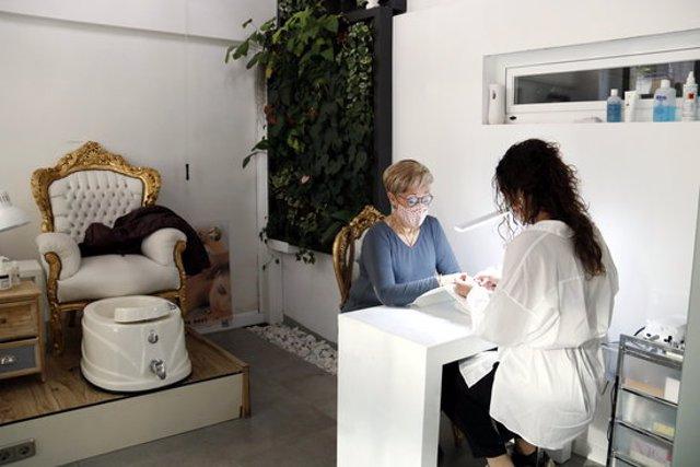 Pla obert de l'atenció a la primera clienta del centre d'estètica Rosa Torrent de Lleida en el primer dia de reobertura. Imatge del 14 de novembre de 2020. (Horitzontal)