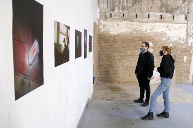 Una de les fotògrafes que exposen a l'Emotiva, Míriam Lázaro, amb un dels membres de Xafa't, a l'espai del Galliner, el 14 de novembre de 2020 (horitzontal)