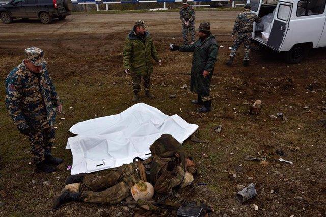 Militares armenios junto al cuerpo de un soldado azerí en Nagorno Karabaj
