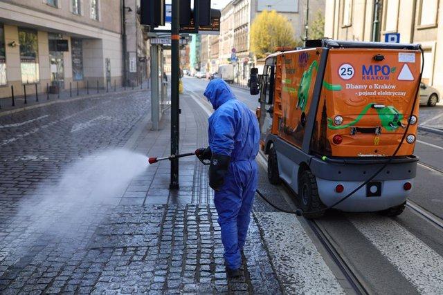 24 March 2020, Poland, Krakow: A worker sprays disinfectant towards a street as a preventive measure against the Coronavirus (Covid-19) outbreak. Photo: Filip Radwanski/SOPA Images via ZUMA Wire/dpa