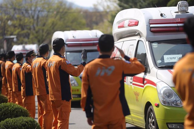 02 April 2020, South Korea, Daegu: Rescue workers in virus-hit Daegu wave toward ambulences carrying their colleagues temporarily mobilized from other areas as they return to their original workplaces after completing their months-long mission to transpor