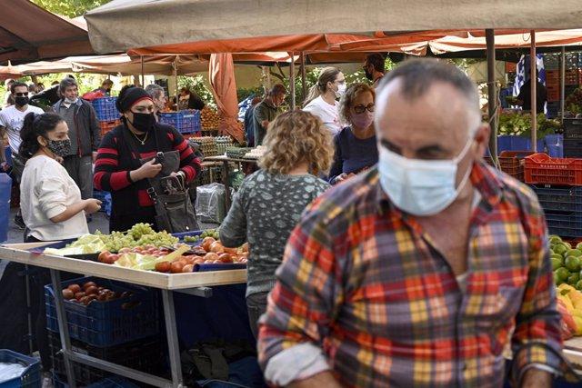 Personas con mascarilla en un mercadillo de Atenas, Grecia
