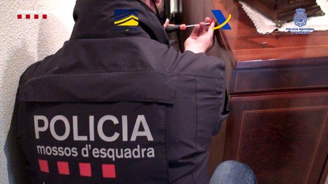Un agent dels Mossos d'Esquadra en un dels escorcolls domiciliaris a l'organització criminal dedicada al contraban d'armes i explosius (Horitzontal).