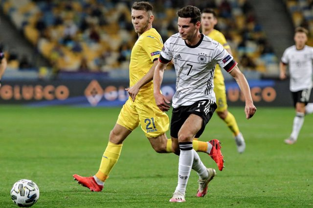 10 October 2020, Ukraine, Kiev: Germany's Julian Draxler (R) and Ukraine's Oleksandr Karavayev battle for the ball during the UEFA Nations League Group D soccer match between Ukraine and Germany at the NSC Olimpiyskiy stadium. Photo: -/Ukrinform/dpa