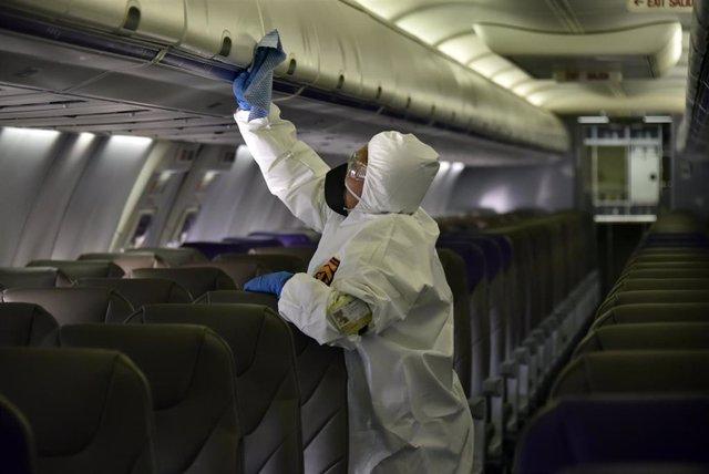 Un trabajador limpia el interior de un avión en el aeropuerto de Bogotá