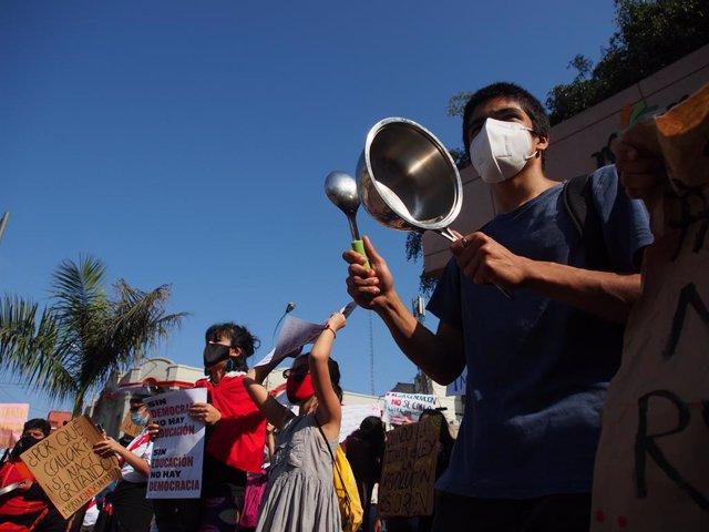 14 November 2020, Peru, Lima: A protester hits a saucepan during a protest against the impeachment of President Martin Vizcarra. Photo: Carlos Garcia Granthon/ZUMA Wire/dpa