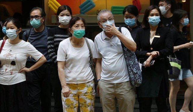 Un grupo de personas esperando para cruzar una calle de Hong Kong