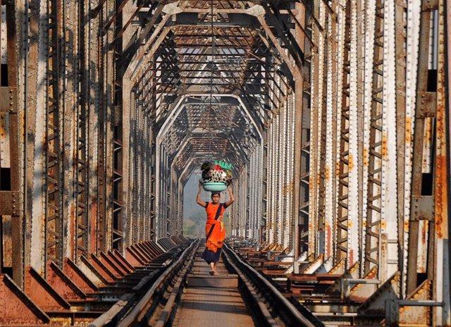 12 November 2020, India, Mumbai: A woman carries luggage as she walks along the railway track. Photo: Ashish Vaishnav/SOPA Images via ZUMA Wire/dpa