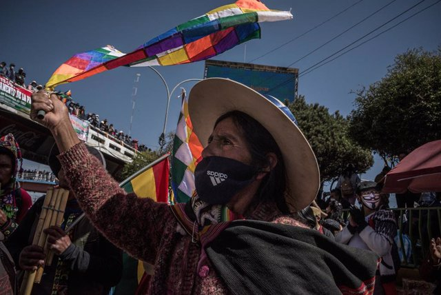 28 July 2020, Bolivia, El Alto: A woman waves the Wiphala flag, representing some native peoples of the Andes, during a protest against the renewed postponement of the general elections. The Supreme Electoral Court had postponed the elections scheduled fo