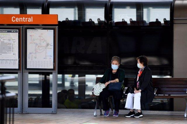 Dos personas con mascarilla esperando al transporte público en Sídney, donde ya no es obligatorio el uso de la mascarilla