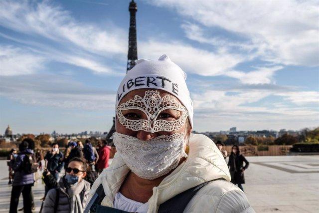 Una simpatizante del movimiento de los 'chalecos amarillos' con mascarilla junto a la Torre Eiffel de París