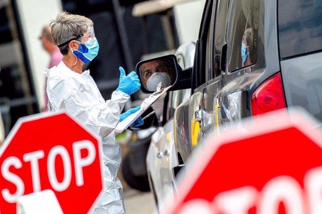 12 May 2020, US, Fontana: A health worker gestures after screening a driver during a coronavirus drive-thru testing at the Auto Club Speedway. Photo: Watchara Phomicinda/Orange County Register via ZUMA/dpa