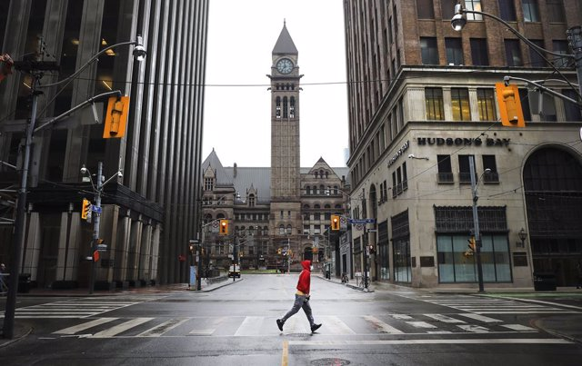 13 April 2020, Canada, Toronto: A man runs across an empty intersection of Bay street and Richmond amid restrictions on public life and non-esseential activities to curb the spreading of coronavirus. Photo: Richard Lautens/The Toronto Star via ZUMA Wire/d