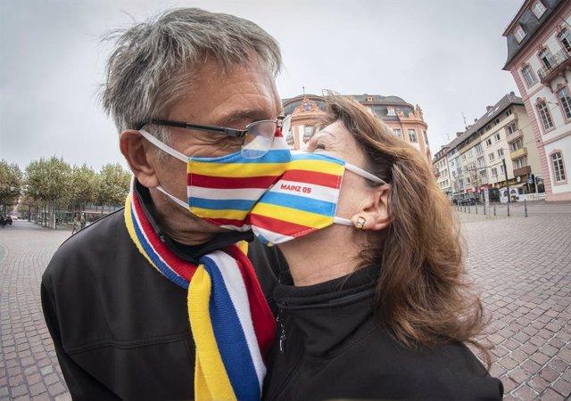 Dos artistas con mascarilla se besa en una plaza de Maguncia