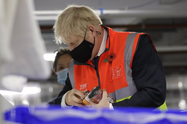 11 November 2020, England, Erith: UK Prime Minister Boris Johnson wearing a face mask loads produce into baskets during a visit to the Tesco Erith distribution Centre in south east London. Photo: Kirsty Wigglesworth/PA Wire/dpa