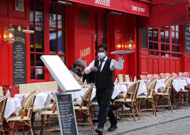 Un camarero en una terraza en París