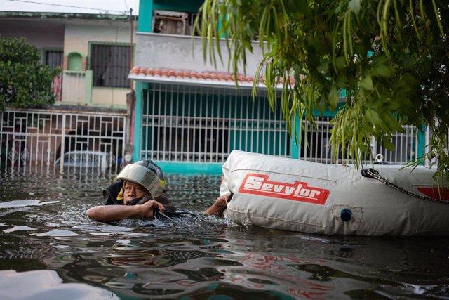11 November 2020, Mexico, Villahermosa: A rescuer runs through a flooded street after heavy rains hit the Tabasco state.. Photo: Armando Vega/dpa