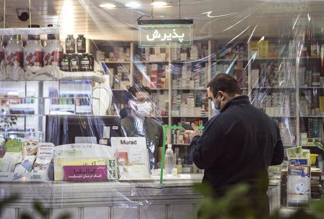 Personas con mascarilla en una farmacia de Mashhad, Irán